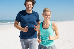 Couple jogging on beach Stock Photos