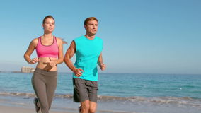 Couple jogging on beach. Slow motion of couple jogging on beach with sea view stock video