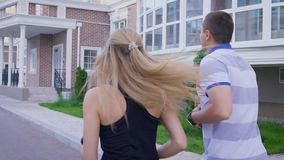 Couple jogging in the city. Man and woman doing sports. Sport and recreation. Slow motion. Back view stock footage