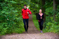 Couple jogging on dirt path in the woods Stock Image