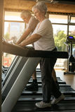 Couple on jogging machine. Senior couple workout in the g Stock Photos