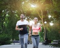 Couple jogging outdoors working out in the park Stock Photos