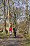 Couple jogging through park. Couple jogging through avenue of trees on sunny spring day Stock Photo