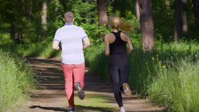 Couple jogging in the park. Sport and healthy lifestyle. Green grass and trees. Slow motion. Back view stock video