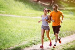 Couple jogging outdoors. Couple jogging and running outdoors in nature stock photo