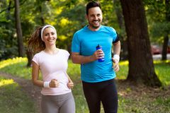 Happy couple jogging and running outdoors in nature stock photography