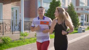 Couple jogging in the street. Running in the city. Man and woman doing sports. Urban sports. Slow motion stock video