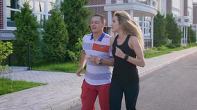 Couple jogging in the street. Running in the city. Man and woman doing sports. Urban sports. Slow motion stock footage