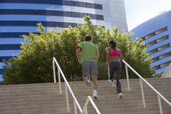Couple jogging up steps in urban setting, rear view Royalty Free Stock Photography
