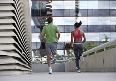 Couple jogging on urban elevated walkway, running side by side, rear view, surface level Stock Photos