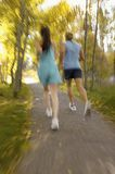 Couple jogging through woods Royalty Free Stock Photo