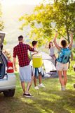 Couple join friends on a camping trip. Happy couple join friends on a camping trip royalty free stock images