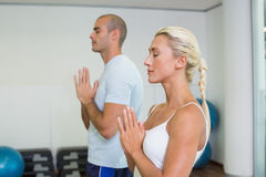 Couple with joined hands and eyes closed at fitness studio Stock Photo