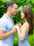 Couple joins hands near blossomed tree Stock Images