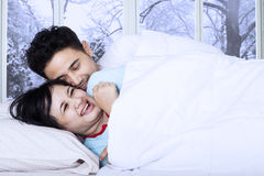 Couple joking on bed in winter day Royalty Free Stock Photography