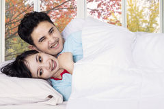 Couple joking and laughing on bedroom Stock Images