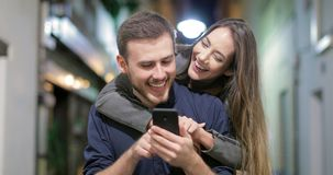 Couple joking watching phone content in the night. Front view of a happy couple walking towards camera joking watching smart phone content in the night in the stock video footage