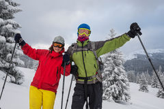 Couple of joyful travelers in goggles stands at alpine meadow. Among snow covered hills, hugging and admires stunning views. Magic adventure in the winter Royalty Free Stock Photos