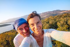 Couple of joyful travelers taking selfie in the mountains stock images
