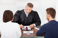 Couple with judge in court. Rear view of couple with judge writing at desk in court royalty free stock photos