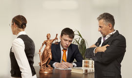 Couple with judge writing at desk in court Stock Images