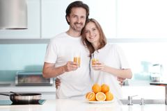 Couple with juice in the kitchen stock image