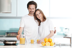 Couple with juice in the kitchen Stock Photography