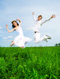 Couple jump in a meadow Royalty Free Stock Photo