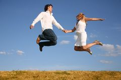 Couple jump on meadow royalty free stock images