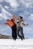 Couple jump over blue sky. In winter Royalty Free Stock Photography