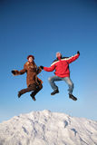 Couple jump on top of snow hill Royalty Free Stock Photo