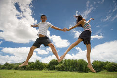 Couple jumping. A man and woman wearing shorts and barefoot jumping against the blue cloudy sky Royalty Free Stock Photography