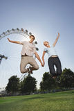 Couple Jumping In Air Against London Eye At Park Royalty Free Stock Images