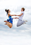 Couple jumping in air against sky. Royalty Free Stock Photos