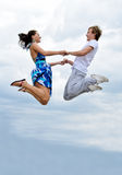 Couple jumping in air against sky. Stock Photo