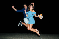 Couple jumping in the air on the beach at night. Happy young couple jumping in the air on the beach at night royalty free stock image