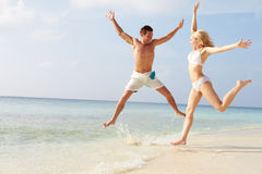 Couple Jumping In The Air On Tropical Beach Stock Photos