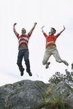 Couple Jumping With Arms Raised Over Rock Royalty Free Stock Image