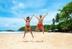 Couple jumping on a beach Royalty Free Stock Images