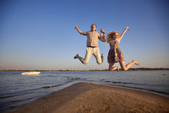 Couple jumping on the beach Royalty Free Stock Photos
