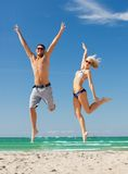 Couple jumping on the beach Stock Images