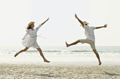 Couple Jumping on Beach. Man and woman jumping on the beach in front of the ocean Royalty Free Stock Image
