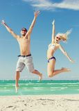 Couple jumping on the beach Stock Photo