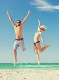 Couple jumping on the beach Stock Photography