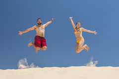 Couple jumping at the beach Stock Photo