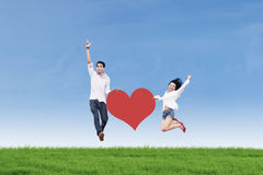 Couple jumping with heart card Stock Photo