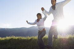 Couple Jumping While Holding Hands In Park Royalty Free Stock Photography