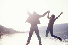Couple jumping in lake Stock Photo