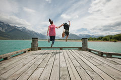 Couple jumping off a jetty fully clothed. Conceptual image of a couple jumping off a jetty together hand in hand stock image