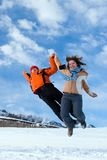 Couple jumping over blue sky in winter mountains Stock Photo